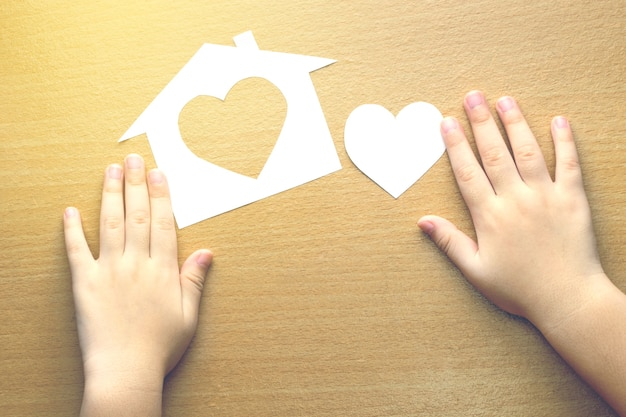 Children hands with small model of house and heart on wooden background