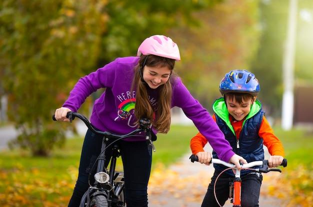 Дети веселятся. сестра учит своего младшего брата кататься на велосипеде в осеннем парке. семья и здоровый образ жизни.