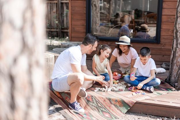 Дети веселятся на летних каникулах на улице играют во дворе возле деревянного дома
