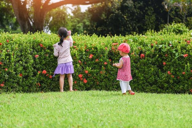 花の木と庭の公園で幸せなアジアの子供女の子の外で遊んで楽しんでいる子供たち