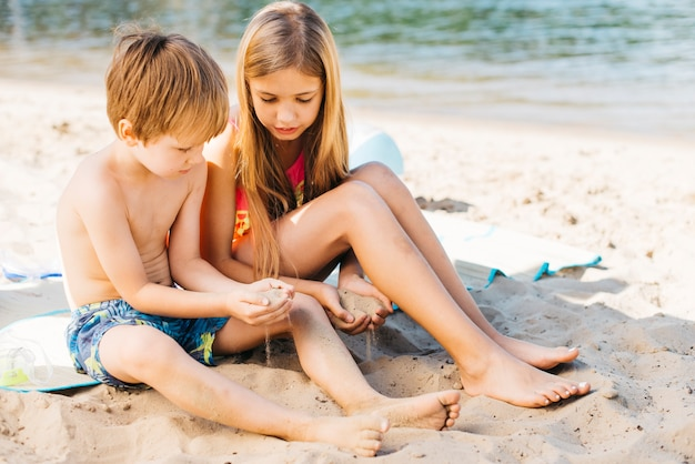 Дети веселятся с песком на берегу