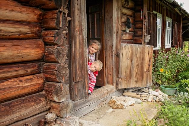 夏休みに古い木造住宅の玄関先で休む子供たち、環境にやさしい旅行コンセプト