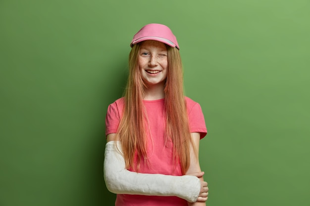 Children and health care concept. cheerful redhead girl poses with broken arm in cast, got injury after falling or accident on road, dressed in summer t shirt and cap, winks eyes, forgets about trauma