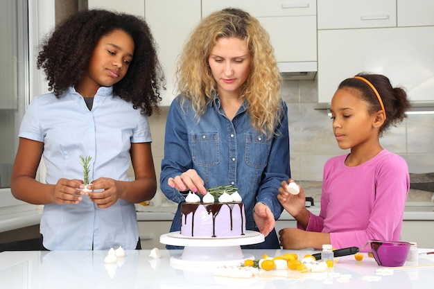Children help mom decorate the cake