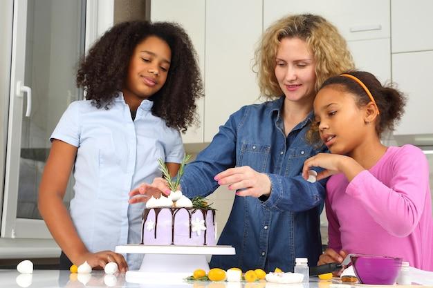 아이들은 엄마가 케이크를 장식하도록 돕습니다.