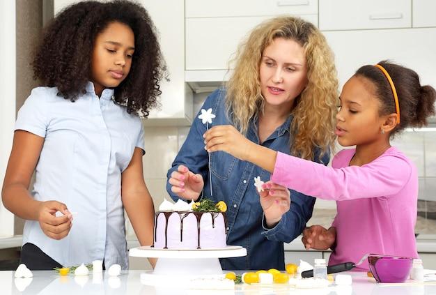 子供たちはお母さんがケーキを飾るのを手伝います