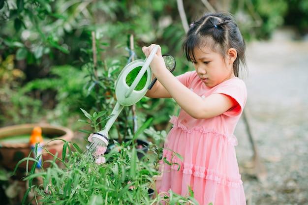 식물에 물을주는 어머니를 돕는 아이들 집에서 원예에 종사