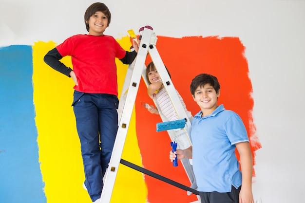 Дети помогают рисовать стену дома