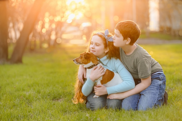 Children her friend a dog in outdoors. friendship, animal protection, lifestyle concept.