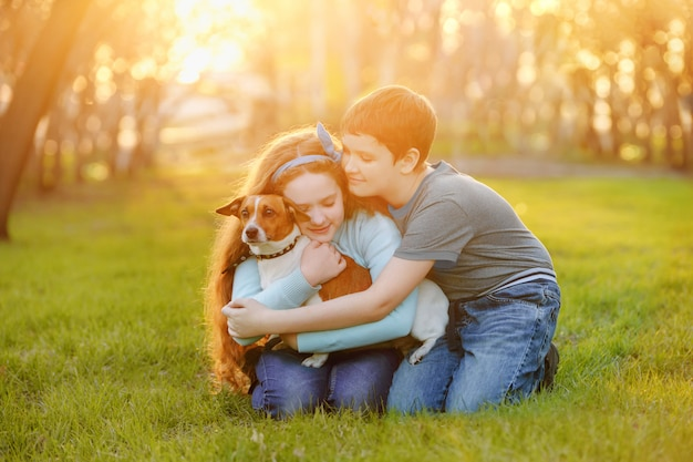 Children her friend a dog in outdoors.