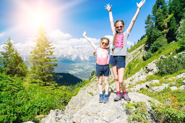Children hiking on beautiful summer day in alps mountains