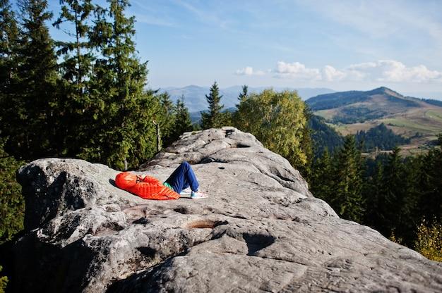 山で美しい日にハイキングをしたり、岩の上で休んだり、山頂の素晴らしい景色を眺めたりする子供たち。子供とのアクティブな家族の休暇の余暇。屋外の楽しさと健康的な活動。