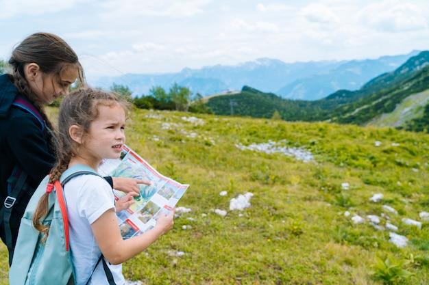 알프스 산맥에서 아름 다운 여름날에 하이킹하는 어린이 오스트리아 바위에 휴식입니다. 아이들은 계곡에서 산봉우리지도를 봅니다. 아이들과 함께 활동적인 가족 휴가 레저. 야외 활동과 건강한 활동