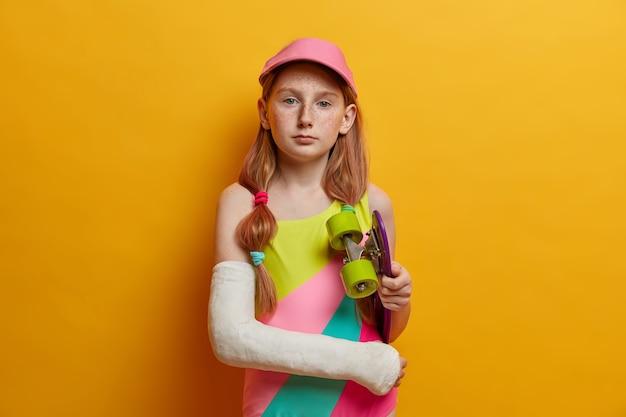 子供、趣味、レクリエーションのコンセプト。深刻なそばかすのある赤毛の女の子がスケートボードでポーズをとり、高速に乗った後にトラウマを負い、極端なスポーツが好きです。チャイルドスケーターがロングボードを腕の下に持つ