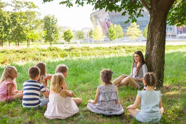 Дети проводят урок с учителем в парке на зеленой лужайке.