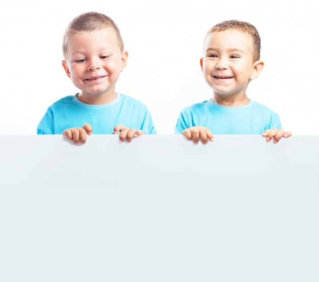 Children holding a blank banner while smiling