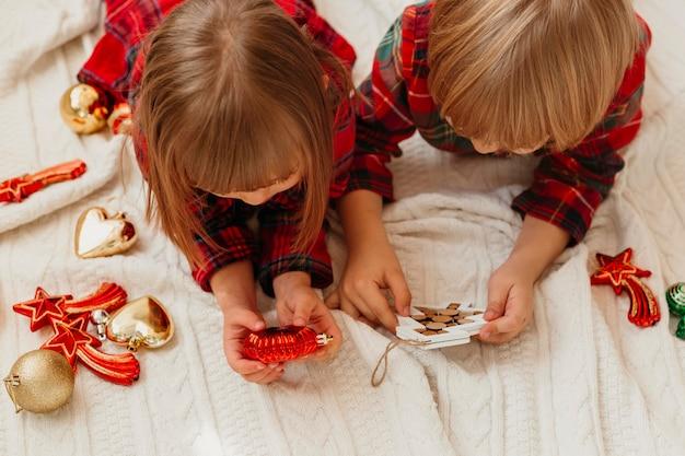 Дети держат рождественские украшения