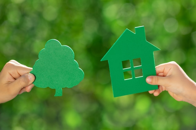 Children holding eco house in hands against spring green background