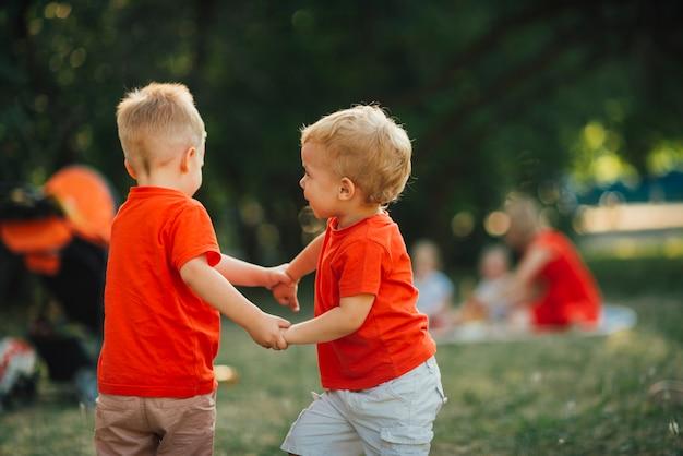 Bambini che si tengono per mano e giocano all'aperto
