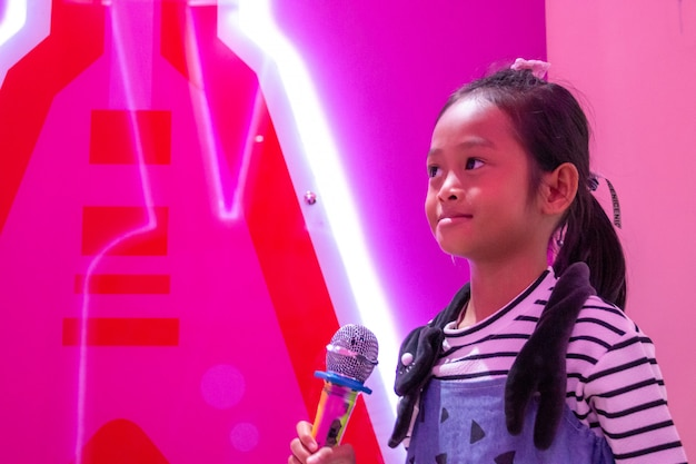 Children holding a microphone singing in the room with neon lights.