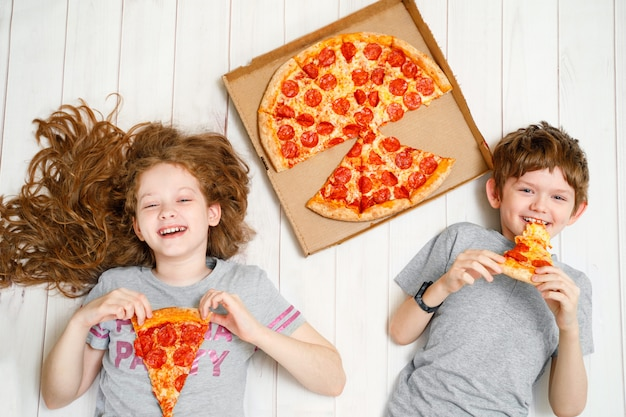 Children holding a slices of pizza lying on the wooden floor