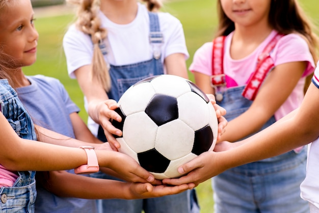 Children holding soccer ball in hands