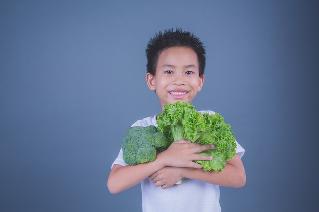 Children holding vegetables on a gray background.