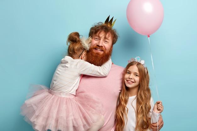 Дети, концепция праздника. веселый папа с рыжей бородой пытается развеселить дочерей на вечеринке, носит младшую дочку на руках, старшая стоит рядом с воздушным шариком, отмечает день рождения или день защиты детей