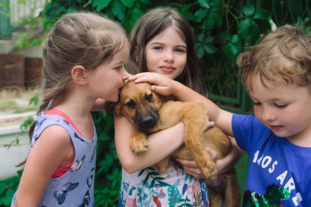 犬を抱きしめてキスする子供たち