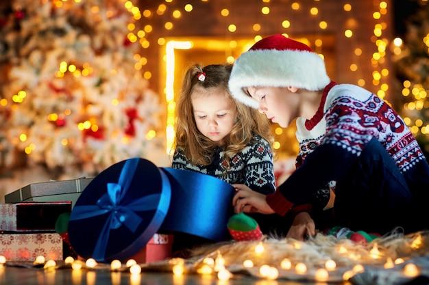 サンタの帽子の子供たちはクリスマスの日に室内の床で遊んで遊びます。
