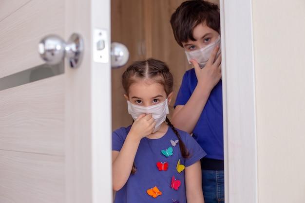 青い服と白い医療用マスクを顔につけた子供たちは、部屋のドアを通り抜けます。