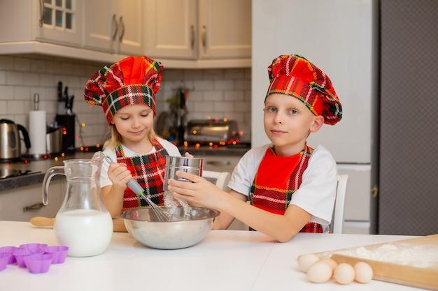 シェフの衣装を着た子供たちは、クリスマスペストリーのために小麦粉のミルクの卵とバターから生地を準備します