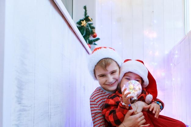 クリスマスツリーのおもちゃでクリスマス衣装を着た子供たち。新年、仮面舞踏会、休日、装飾の概念