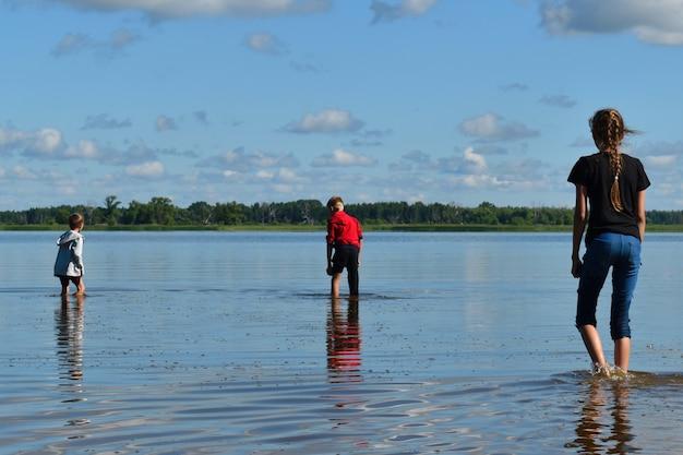 服を着た子供は、大きな川で膝までの費用がかかります。