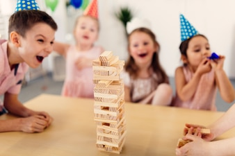 Children in colored caps laughing on party