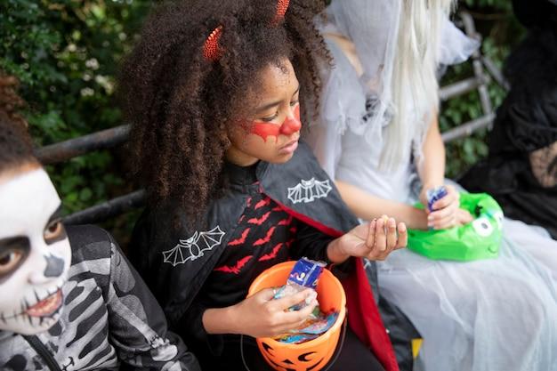 Дети в костюмах едят конфеты