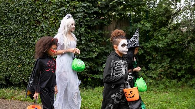 Дети в костюмах собираются пошутить или угостить