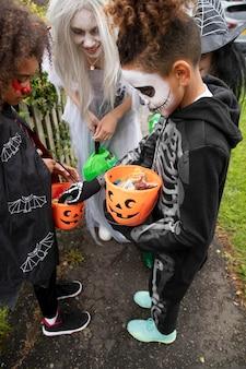 Дети в костюмах смотрят на свои конфеты на хэллоуин