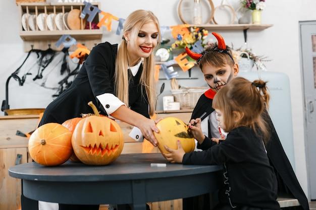 Дети в костюмах на хэллоуин вырезают на тыквах страшные глаза и рты, младшим помогает старшая сестра. фото высокого качества