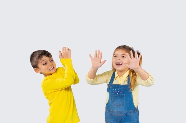 家庭服を着た子供たちは、白い背景の上で楽しんで顔を作っています。