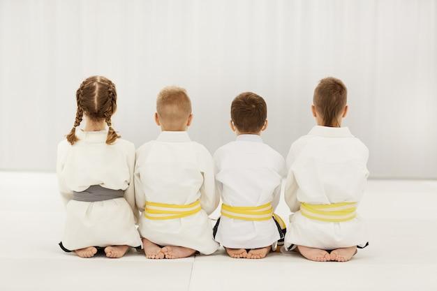 Дети в кимоно занимаются дзюдо