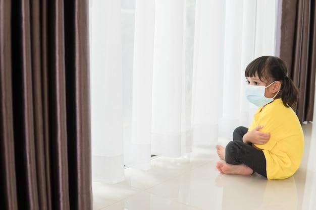 医療用マスクの子供たちは、自己検疫のために自宅で隔離されたままになりますコンセプトホーム検疫
