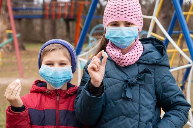 薬を保持している医療マスクの子供たち。小さな男の子と女の子は危険なウイルスから身を守ります。ビタミン摂取のコンセプト