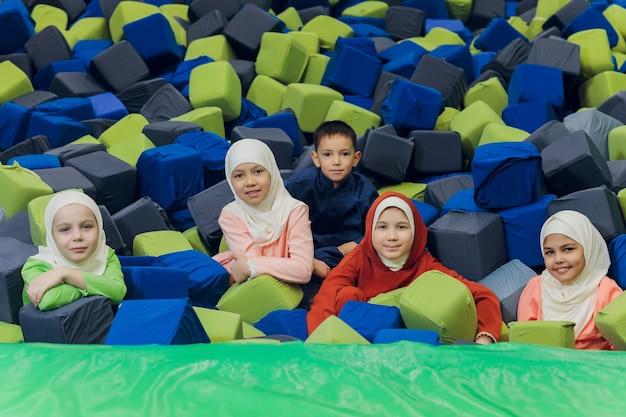 Дети в мусульманской одежде прыгают в мягких кубиках.