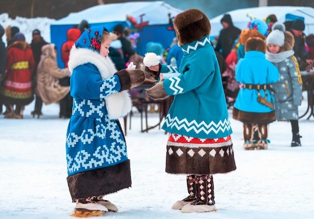 Дети в национальной одежде едят сахарную вату. праздник день оленей северных народов ханты и манси.