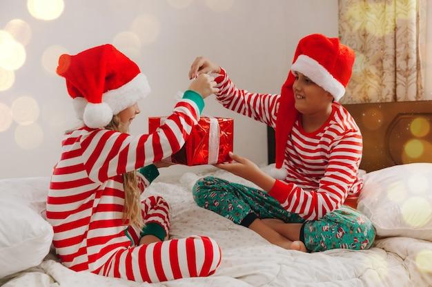 Дети в пижамах и новогодних шапках на кровати с подарками. рождество и новый год концепция