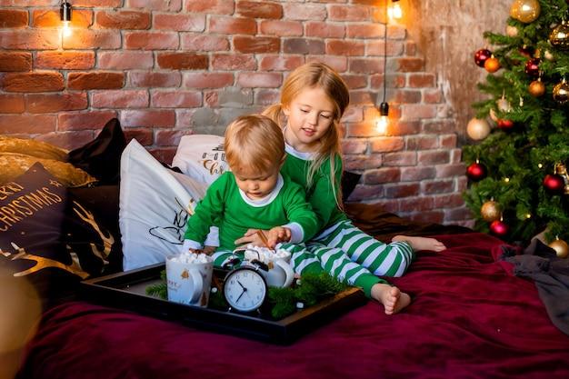 Дети в пижамах с какао возле елки