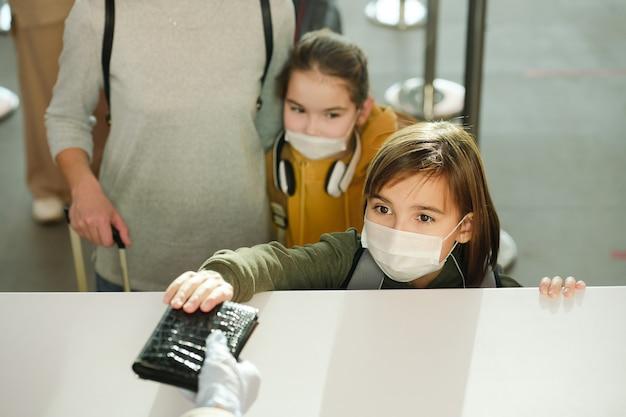 Дети в защитных масках сдают документы на стойке регистрации вместе с матерью