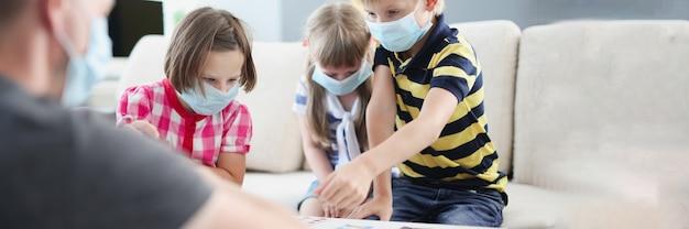 テーブルで両親とボードゲームをしている保護医療マスクの子供たち