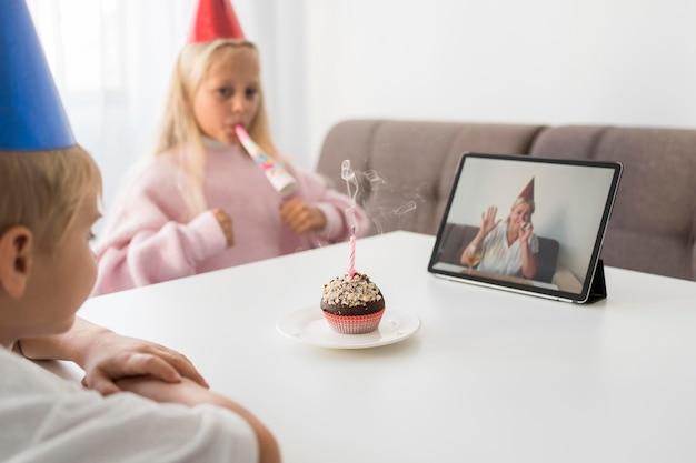 タブレットで誕生日を祝う自宅で検疫中の子供たち
